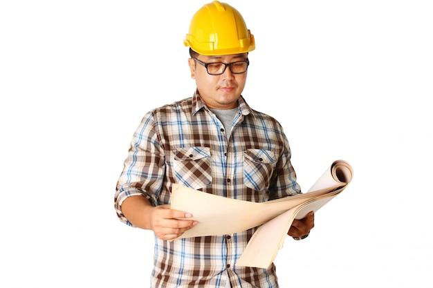 Um capacete usando um capacete amarelo está lendo para construir um edifício.
