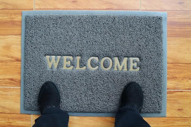 Um capacho cinza de boas-vindas com pés e sapatos pretos