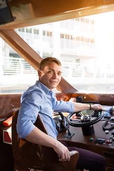 Um capitão do sexo masculino de um barco a motor no leme de um barco