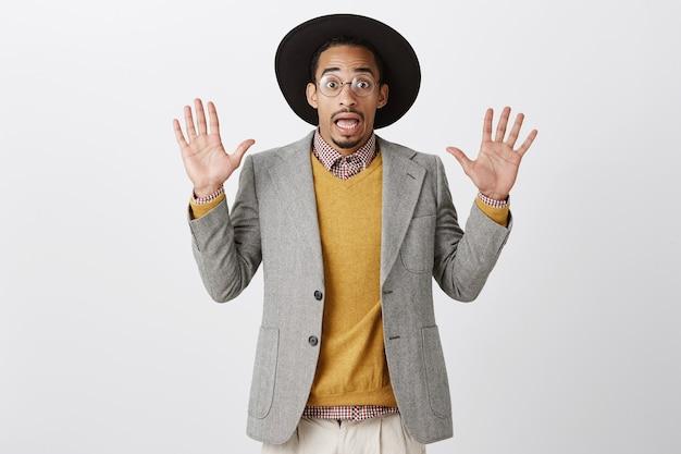 Um cara afro-americano bonito emboscado levantando as mãos em sinal de rendição