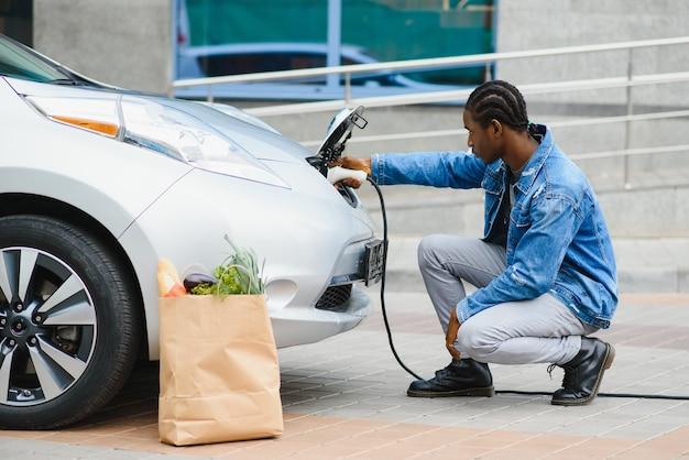 Um cara afro-americano bonito sentado perto de seu novo carro elétrico moderno e segurando o plugue do carregador