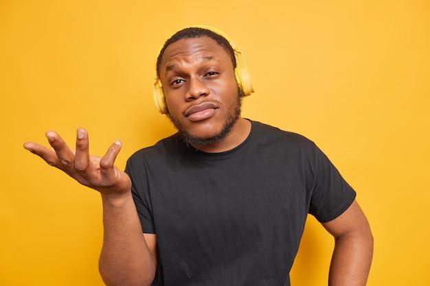 Um cara afro-americano de pele escura confuso e perplexo levanta a palma da mão pergunta e daí