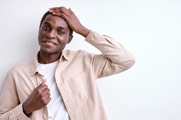 Um cara afro-americano simpático tocando a cabeça e sorrindo, isolado no fundo branco