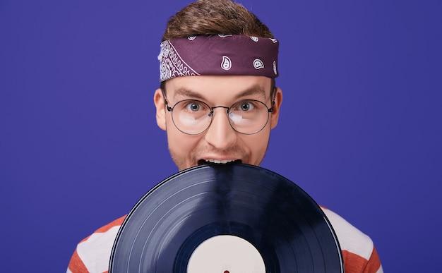 Um cara alegre de óculos morde, brincando, um toca-discos.