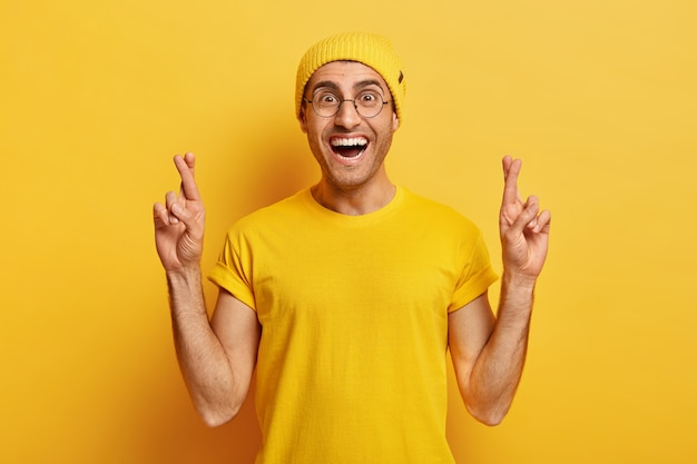 Um cara alegre e esperançoso cruza os dedos para dar sorte