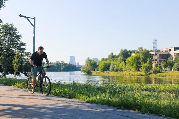 Um cara anda de bicicleta no parque. jovem apto homem durante um passeio de bicicleta em um dia ensolarado. foco turvo