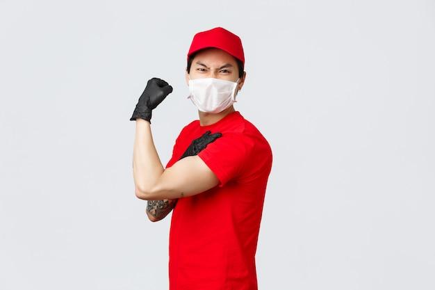Um cara asiático forte mostra sua força, carrega grandes encomendas no trabalho. entregador de uniforme bíceps flexível e fazer caretas, usar máscara e luvas médicas, propaganda da transportadora e entrega de pedidos