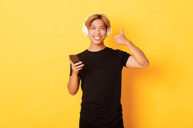 Um cara asiático satisfeito e feliz gosta de música ou podcast, mostrando o polegar para cima em aprovação, segurando um telefone celular, em pé na parede amarela
