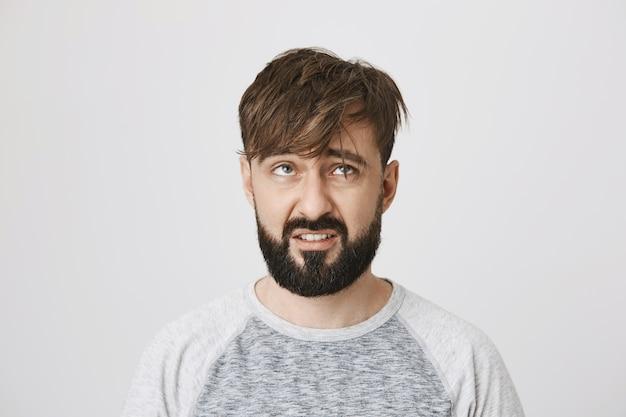 Um cara barbudo bagunçado e sombrio com cabelo despenteado