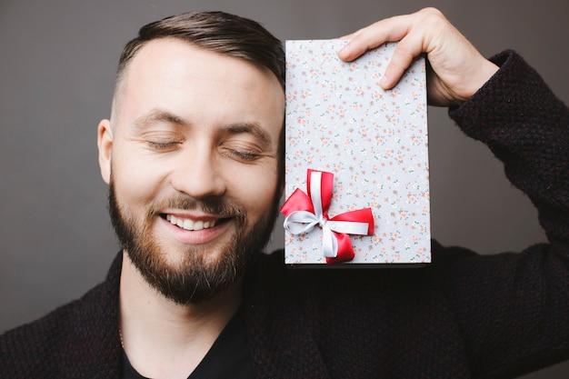 Um cara barbudo bonito sorrindo e mantendo os olhos fechados, segurando um lindo presente perto do rosto e de pé sobre um fundo cinza