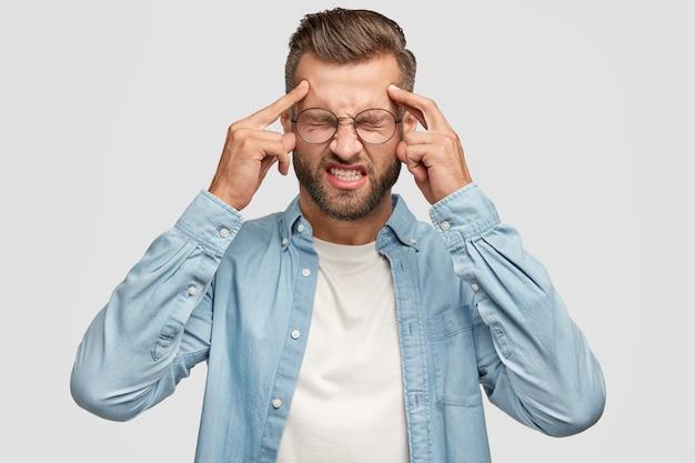 Um cara barbudo desesperado posando contra a parede branca