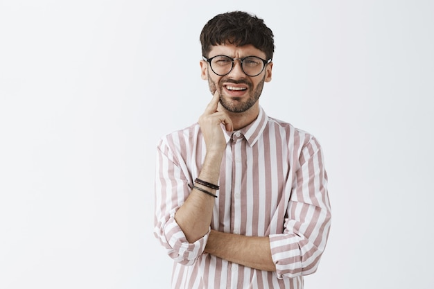 Um cara barbudo elegante e confuso posando contra a parede branca com óculos