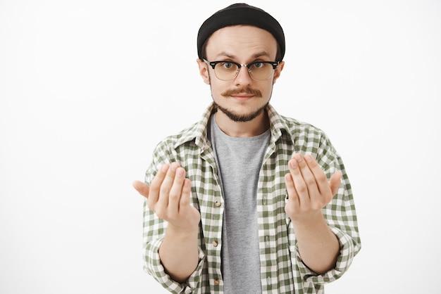 Um cara barbudo habilidoso e sério, de óculos e gorro preto, levantando as palmas das mãos perto do corpo, pedindo para se aproximar dele ou dar algo que queira segurar item nas mãos sobre a parede cinza