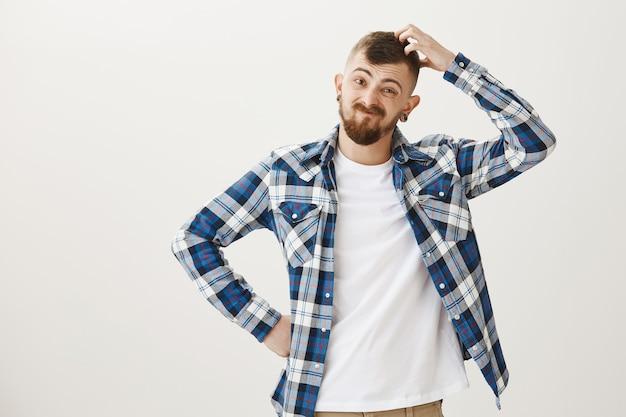 Um cara barbudo sem noção coça a cabeça e sorri indeciso, parecendo inseguro