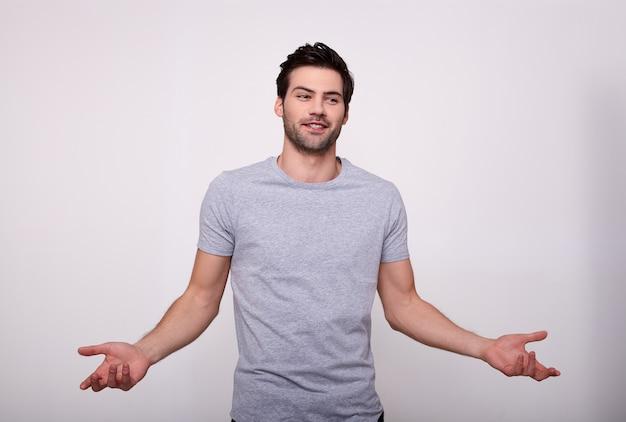 Um cara bonito com as mãos em surpresa, de pé sobre um branco.