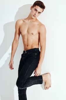 Um cara bonito com um torso nu fica em uma perna contra a parede