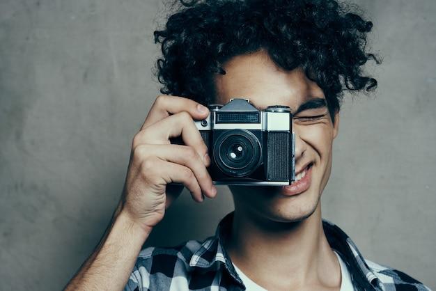 Um cara bonito com uma câmera perto do rosto e cabelo cacheado, camisa xadrez, fotógrafo amador