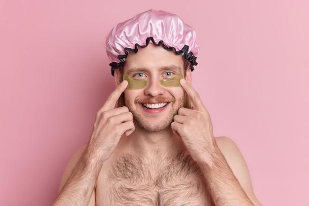 Um cara bonito e alegre com a barba por fazer indica manchas de hidrogel embaixo dos olhos e reduz as rugas com um sorriso feliz no rosto