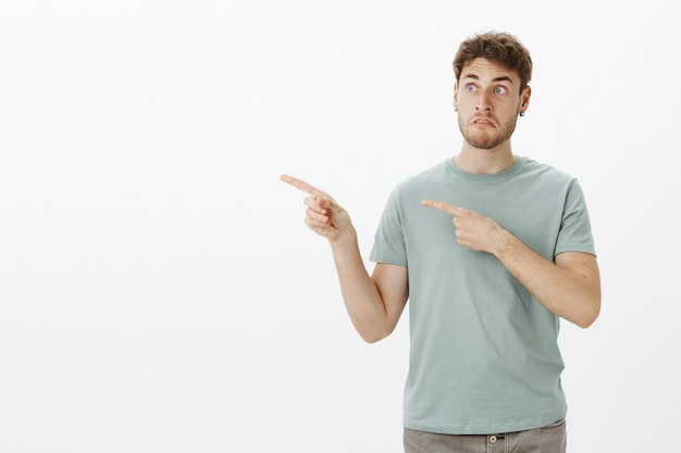 Um cara bonito e engraçado, confuso e atordoado, com cabelo loiro em uma camiseta da moda, apontando e olhando para a esquerda com uma cara estranha e questionada
