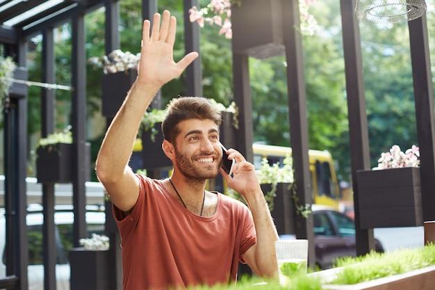 Um cara bonito e sorridente falando ao telefone e acenando para a garçonete em um café ao ar livre, pedindo a conta