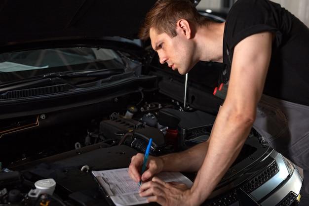 Um cara bonito está fazendo anotações enquanto conserta o capô do carro