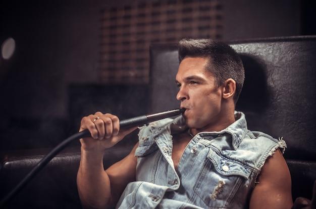 Um cara bonito fuma um narguilé oriental perfumado no bar.