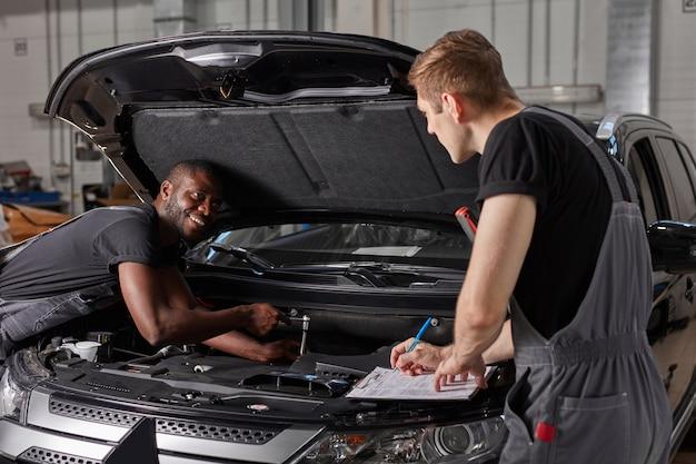 Um cara caucasiano bonito está fazendo anotações enquanto conserta o capô do carro