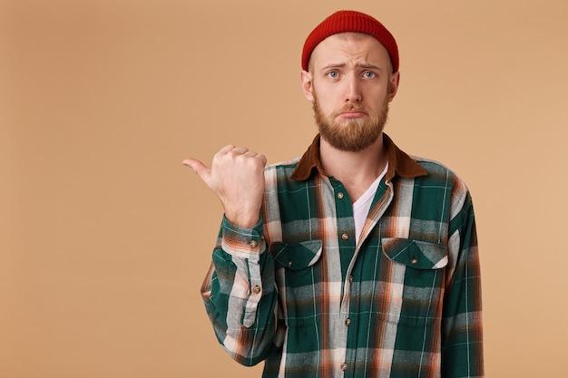 Um cara chateado com uma expressão triste nos olhos e uma expressão facial descontente mostra o polegar