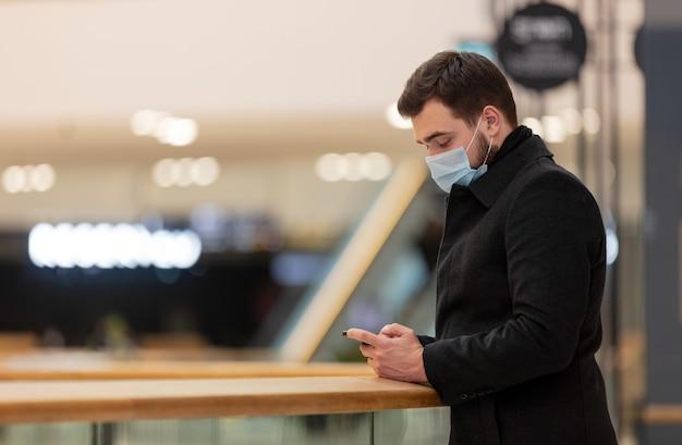 Um cara com máscara facial e casaco está usando o telefone celular no shopping da cidade em época de pandemia