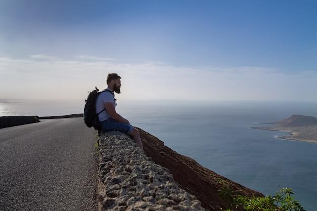 Um cara com roupas de verão está sentado em uma cerca de pedra e olha para uma ilha próxima no oceano. mirador del rio, lanzarote, espanha.