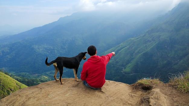 Um cara com um cachorro apreciando a paisagem montanhosa à beira de um precipício