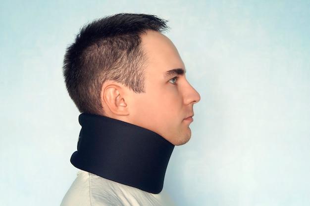 Um cara com um pescoço ruim em uma coleira preta para estabilizar as vértebras cervicais. um homem com uma lesão no pescoço em um fundo azul. fratura da coluna vertebral. jovem usando colarinho no fundo azul