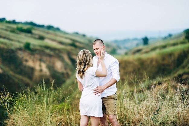Um cara com uma garota com roupas leves no fundo de um desfiladeiro verde da erosão da terra