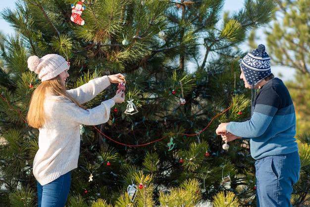 Um cara com uma garota decora uma árvore de natal verde em uma rua no inverno na floresta com brinquedos decorativos e guirlandas, enfeites de árvore de natal