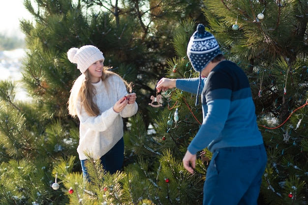 Um cara com uma garota decora uma árvore de natal verde em uma rua no inverno na floresta com brinquedos decorativos e guirlandas