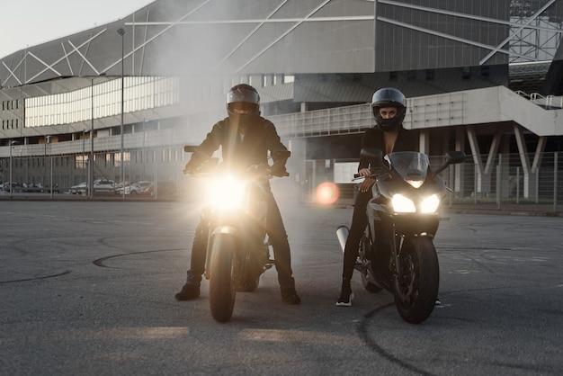 Um cara com uma garota em jaquetas de couro em um estacionamento subterrâneo com uma motocicleta