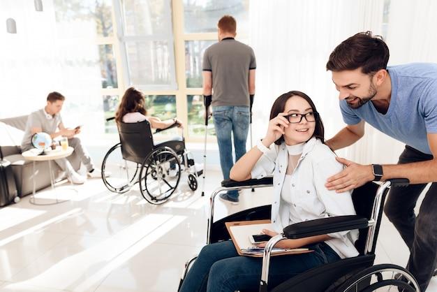 Um cara com uma garota em uma cadeira de rodas está viajando.