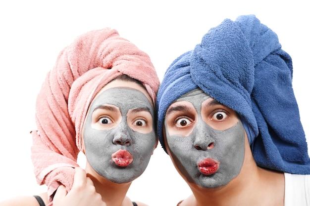 Um cara com uma garota olha para a câmera e manda um beijo no ar, máscara para pele de homem e mulher