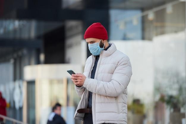 Um cara com uma máscara no rosto usando um smartphone no centro da cidade.