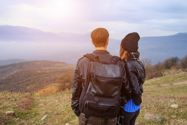 Um cara com uma mochila e uma garota olhando para as montanhas ao longe