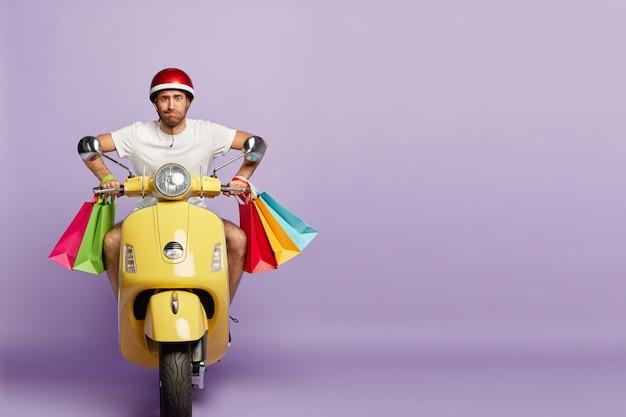 Um cara confiante com capacete e sacolas de compras dirigindo uma scooter amarela