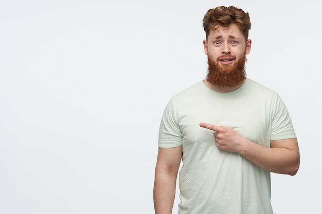 Um cara confuso com barba e cabelo ruivo usa uma camiseta em branco apontando para o lado esquerdo