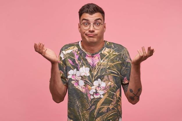 Um cara de cabelo curto atraente e desnorteado com óculos levantando as palmas das mãos para cima com expressão facial complicada, testa contraindo, posando