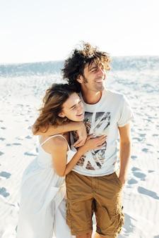Um cara de cabelo encaracolado e sua namorada estão se abraçando alegremente na areia.