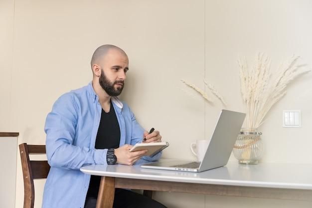 Um cara de camisa azul e calça jeans preta está estudando online em casa, sentado em uma mesa, usando um computador e um diário para escrever