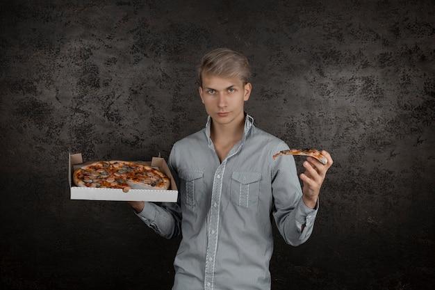 Um cara de camiseta branca tem um pedaço de pizza nas mãos em um fundo preto. jovem comendo uma fatia de pizza com os olhos fechados, isolada em fundo amarelo.