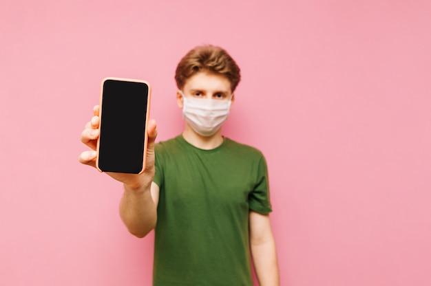 Um cara de camiseta verde e uma máscara de gaze protetora fica de pé e mostra à câmera um smartphone com uma tela preta. pandemia do coronavírus. quarentena. covid19.