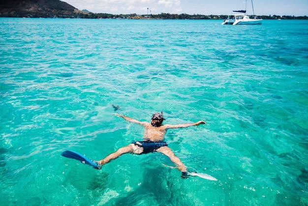 Um cara de nadadeiras e máscara nada em uma lagoa na ilha de maurício.
