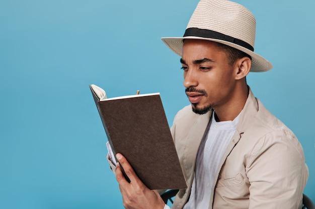 Um cara de pele escura com chapéu olha atentamente para seu caderno