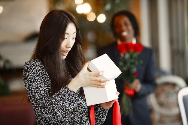 Um cara de pele escura com rosas. garota feliz com um presente. noite romântica em um café.